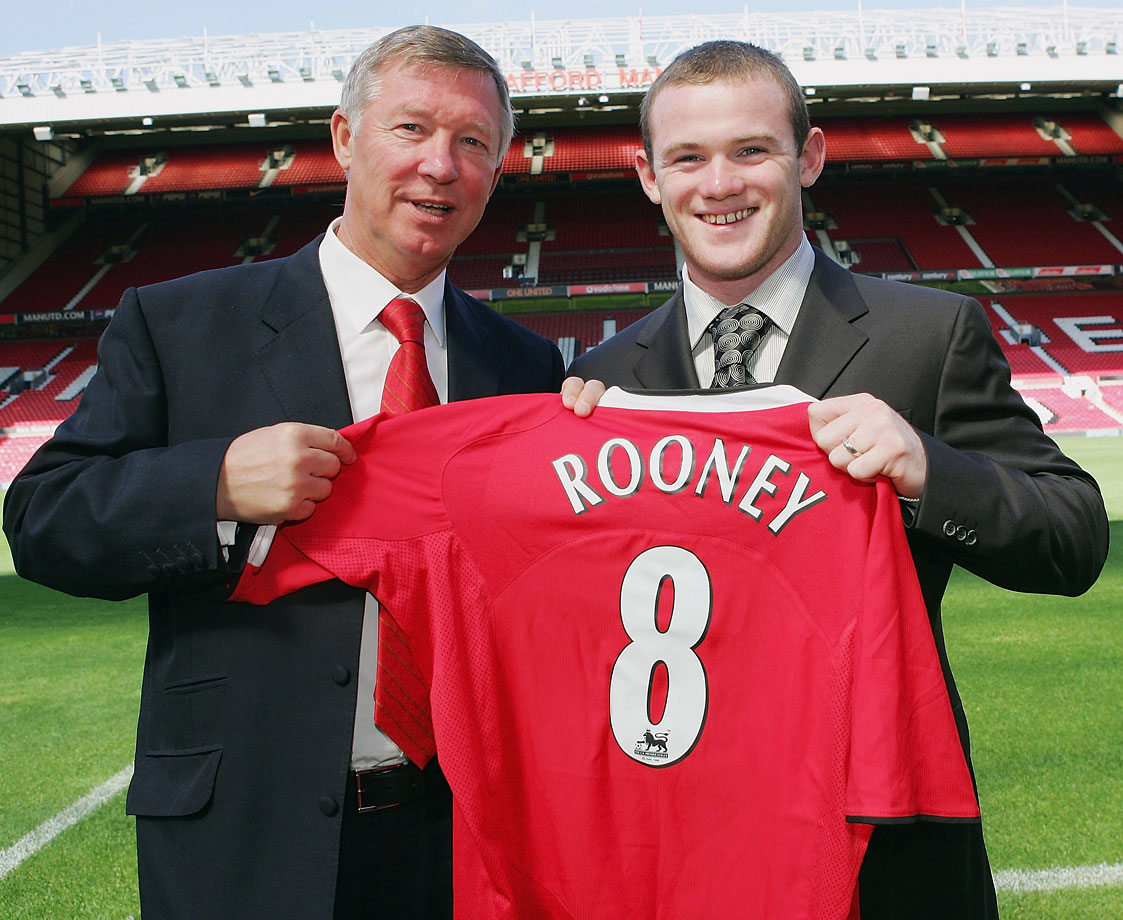 Wayne Rooney with Manchester United manager Sir Alex Ferguson pose together the day after the English striker signed with the club on Sept. 1, 2004.