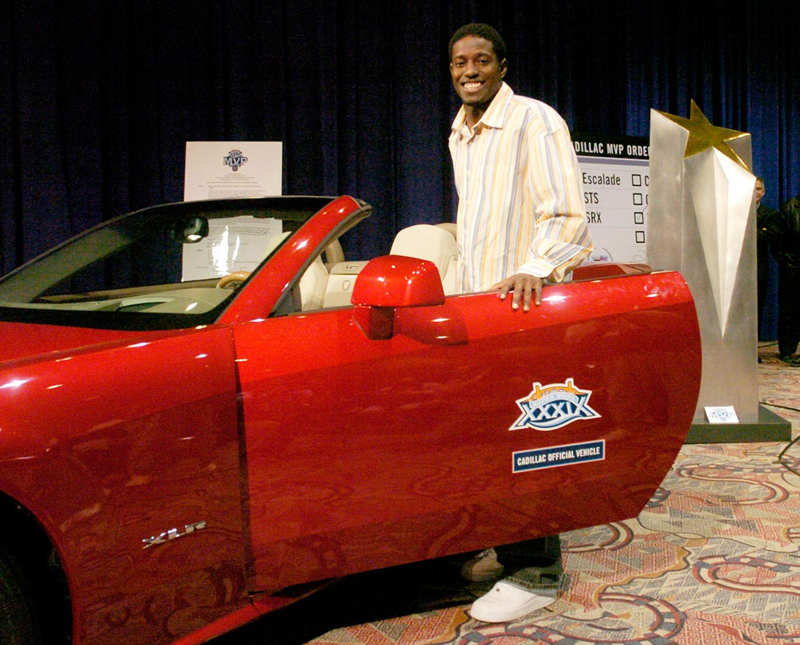 Deion Branch of the New England Patriots stands by a new car he won at Super Bowl XXXIX.