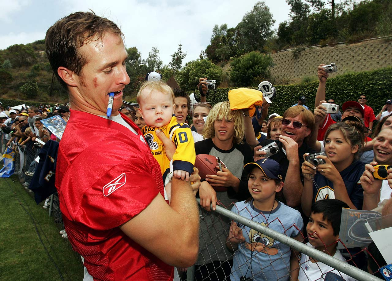 Drew Brees pulls four and a half month old Jacob Anthony Dill out of the crowd to sign the back of his jersey during the San Diego Chargers Mini Camp.
