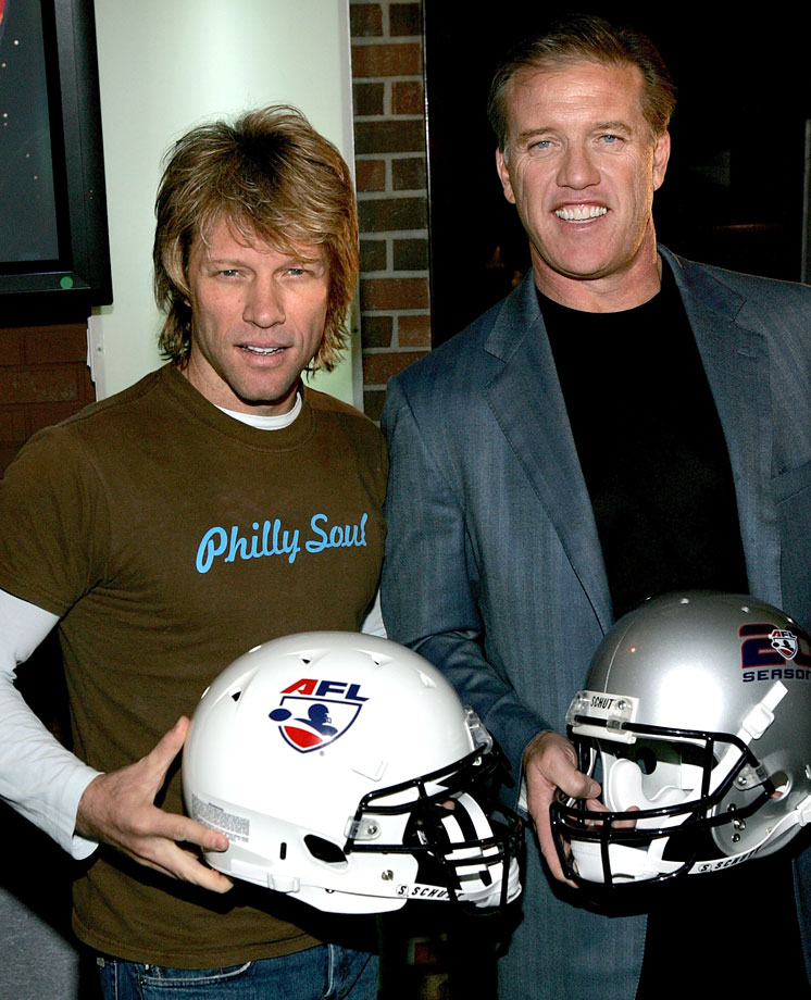 Philadelphia Soul co-owner Jon Bon Jovi and Colorado Crush co-owner John Elway hold Arena Football helmets as they attend a media conference for the AFL's 20th season kick off at the ESPN Zone in New York City.