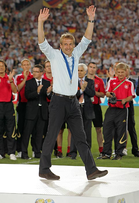 Klinsmann acknowledges the crowd at the medal presentation after winning the third-place game 3-1 over Portugal. Klinsmann would later be named German Football Manager of the Year.