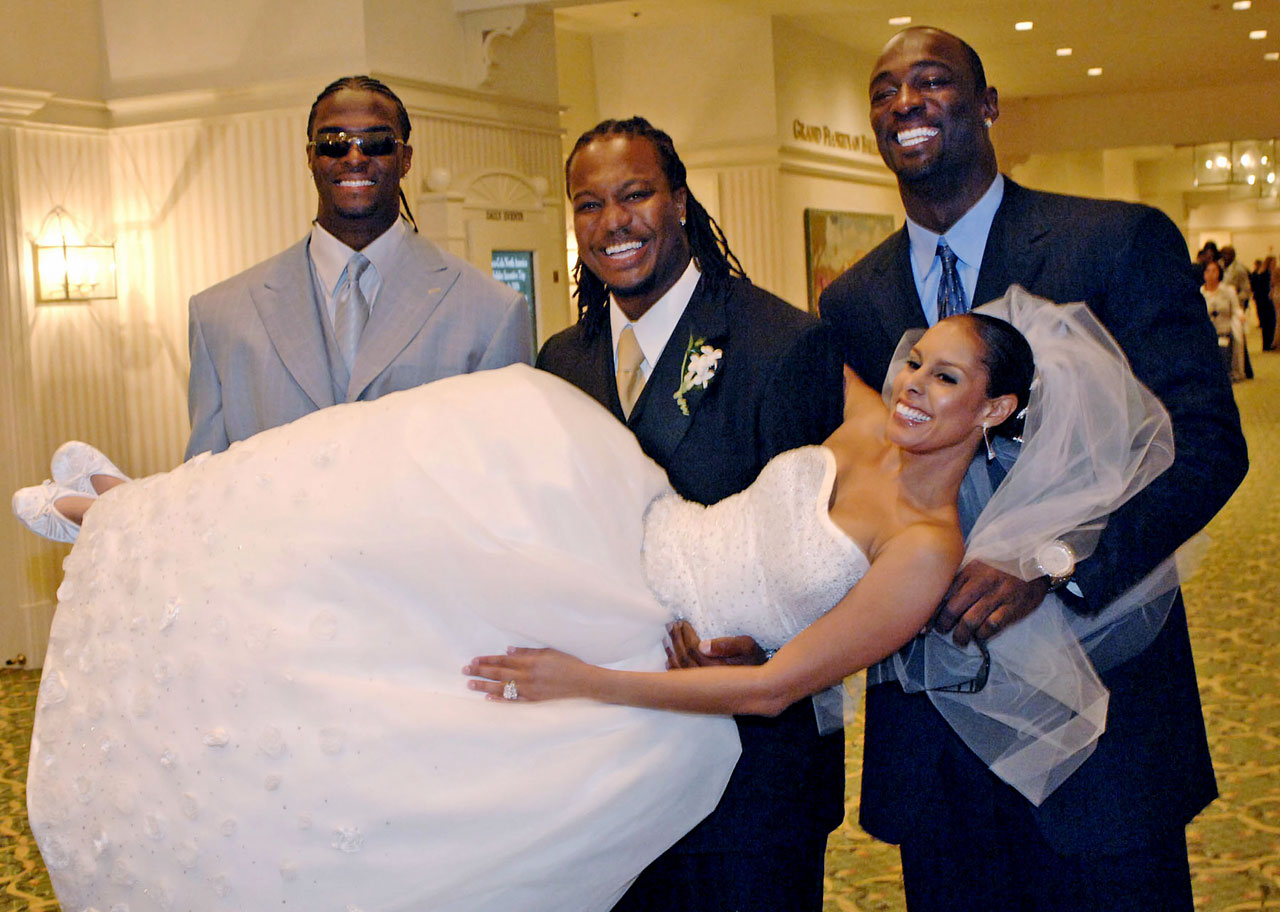 Mike Peterson and Chantal Day, posing with Plaxico Burress (left) and Jevon Kearse (right).