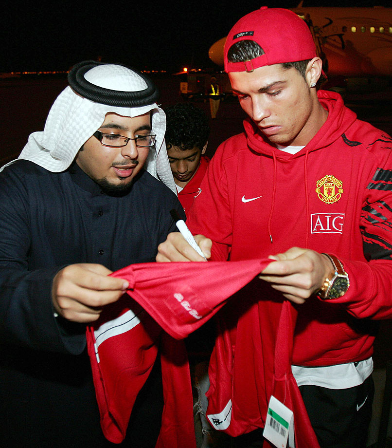 Cristiano Ronaldo autographs a team jersey for a Saudi man after arriving at King Khaled airport in Riyadh, Saudi Arabia.