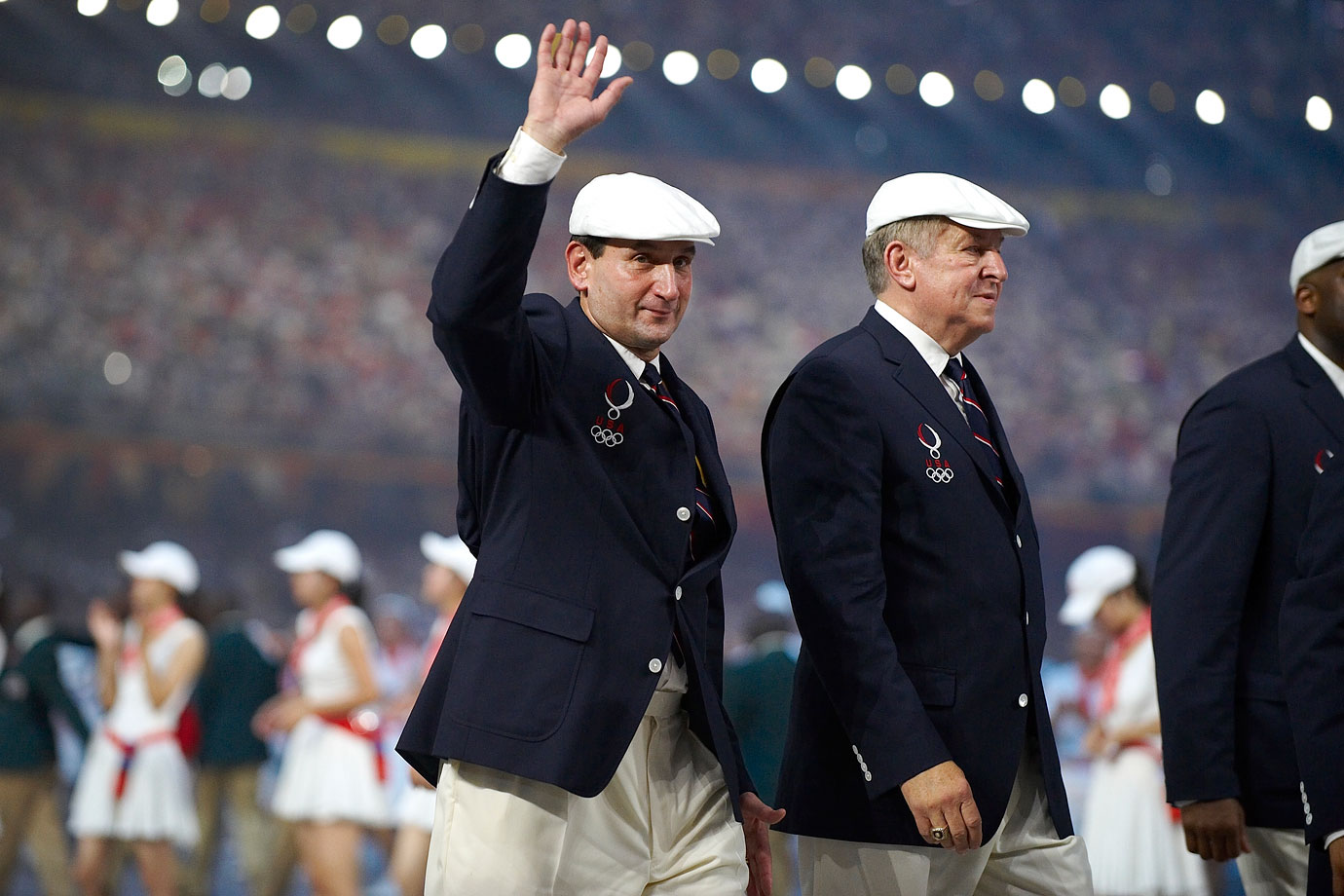 Mike Krzyzewski waves while walking with the Team USA delegation during athlete procession for the 2008 Summer Olympics at National Stadium in Beijing, China.  He would go on to coach the men's basketball team to gold.