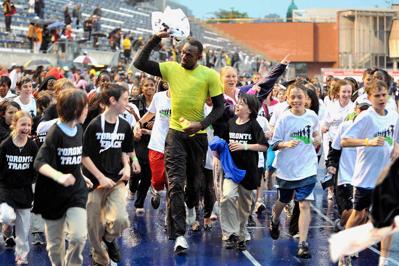 Usain Bolt runs the track with kids at the 2009 Festival of Excellence meet at Varsity Stadium on the University of Toronto Campus in Ontario, Canada.