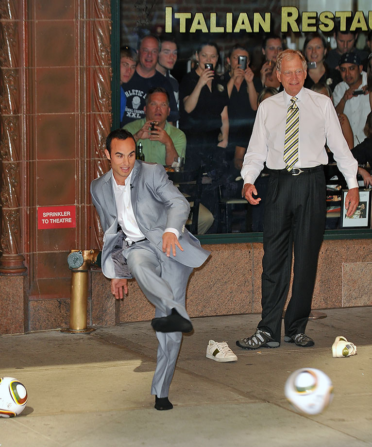 "Landon Donovan and David Letterman take turns trying to kick a ball into the open window of a taxi outside the Ed Sullivan Theater for ""The Late Show With David Letterman."""
