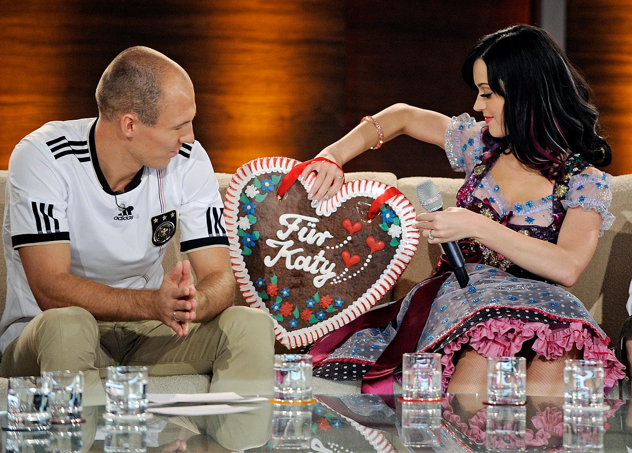 "Katy Perry sits with Arjen Robben during the German TV show ""Bet It"" on Oct. 2, 2010 in Munich, Germany."