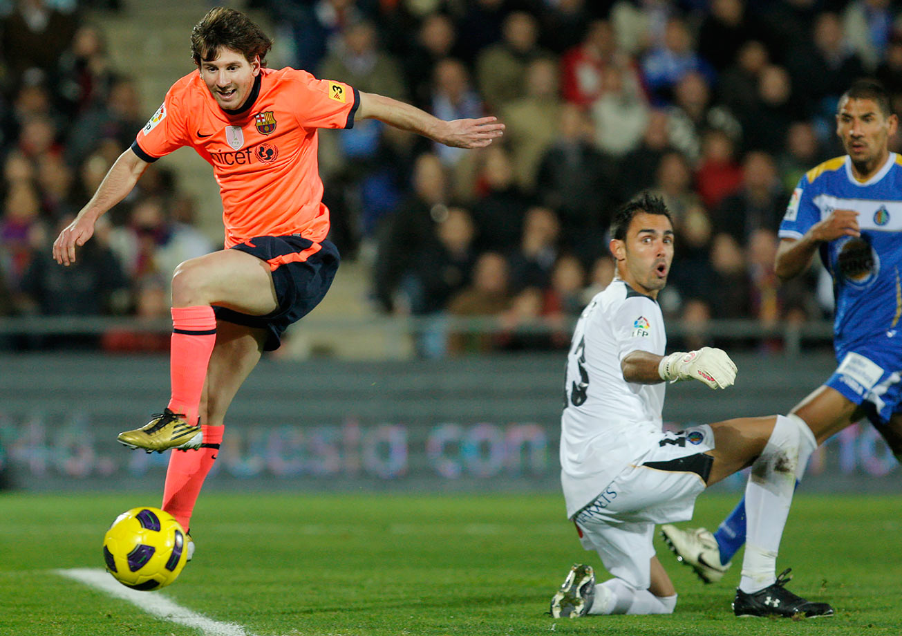 Barcelona's Lionel Messi from vies for the ball with Getafe's goalkeeper Jordi Codina during their La Liga match on Nov. 7, 2010 at the Coliseum Alfonso Perez in Getafe, near Madrid, Spain.