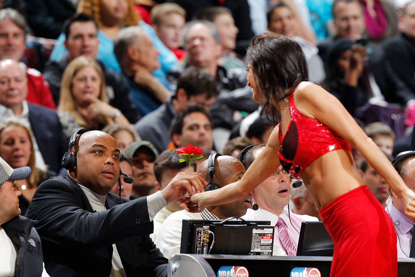 Charles Barkley gives a Chicago Bulls Luvabulls dancer a flower while broadcasting a Bulls-Heat game. Upon retiring from the NBA in 2000, Barkley quickly went into broadcasting, working as both a studio and color analyst for basketball games.