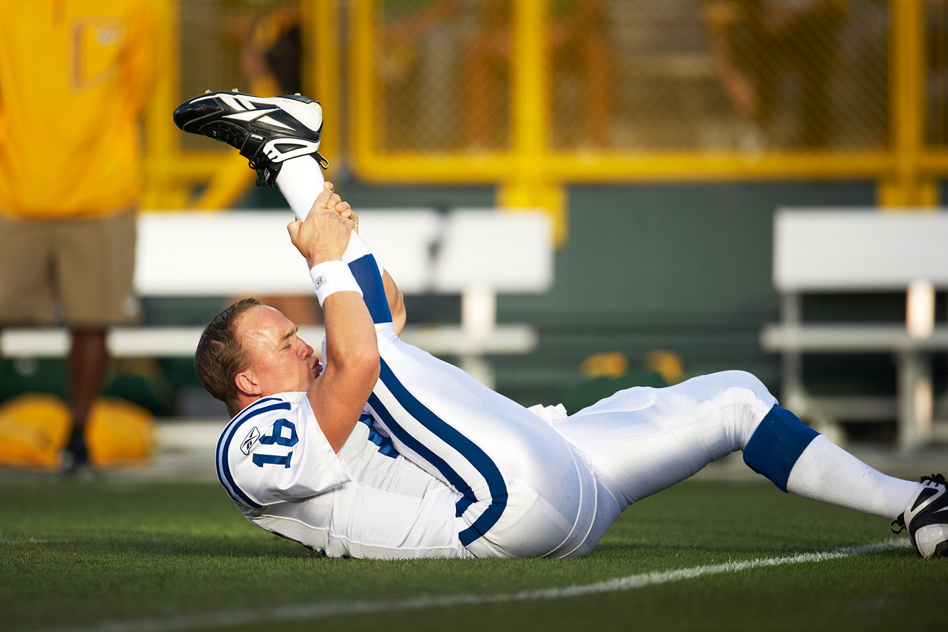 Peyton Manning stretches before a Colts-Packers preseason game in Green Bay.