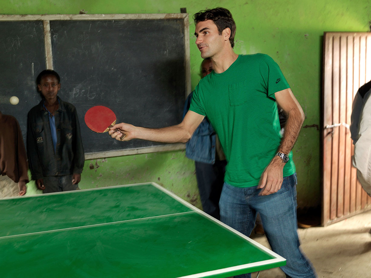 Roger Federer plays table tennis with local school children during his visit to a school funded by his charity, the Roger Federer Foundation, in Kore Roba, Ethiopia, on Feb. 12, 2010.