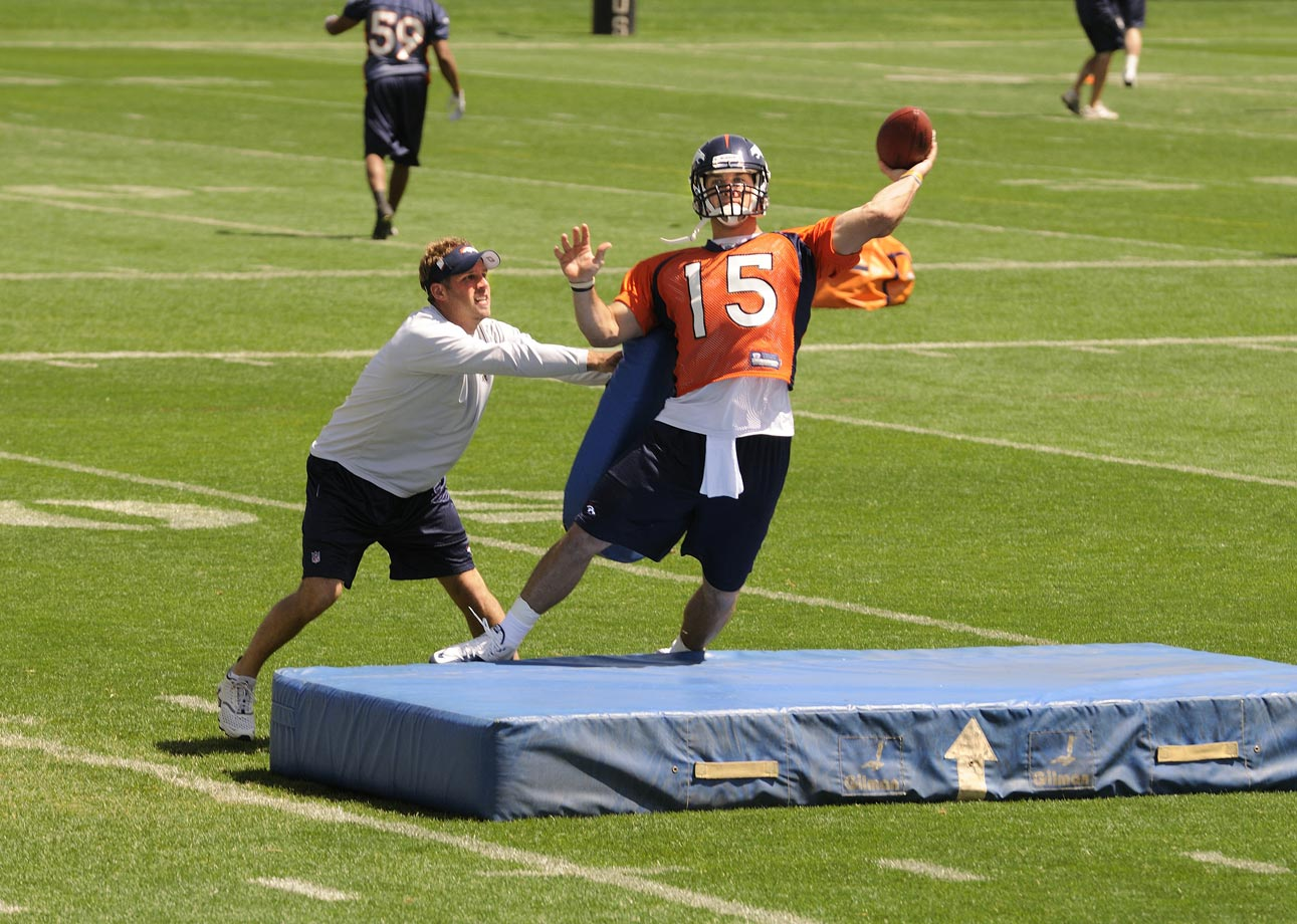 Broncos quarterbacks coach Ben McDaniels pushes Tim Tebow during a passing drill.