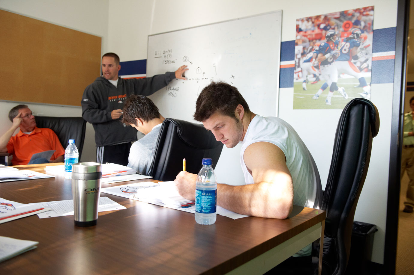 Tim Tebow takes notes at a quarterbacks meeting with Broncos' head coach Josh McDaniels.