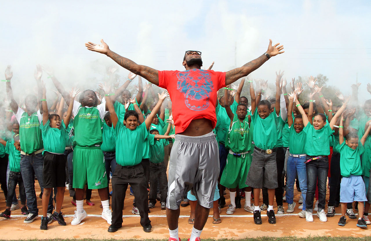 "LeBron joins 200 youth in a spontaneous ""chalk clap"" to dedicate a new athletic field at the Boys & Girls Club of Central Florida in 2010."