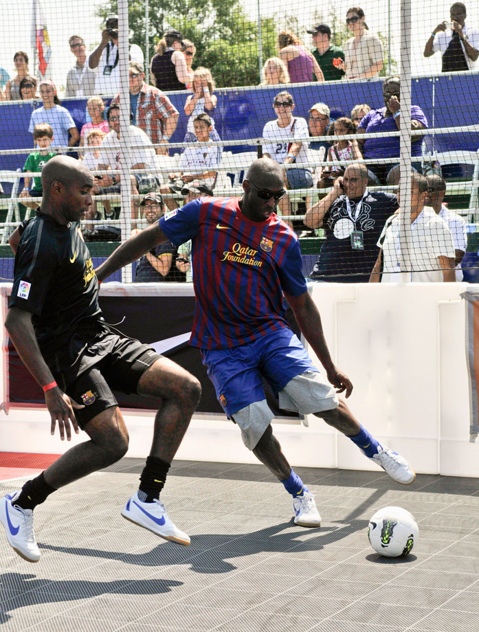 Eddie Pope and Bryant fight for the ball during the 2011 Celebrity Soccer Challenge at Kastles Stadium in Washington, D.C.