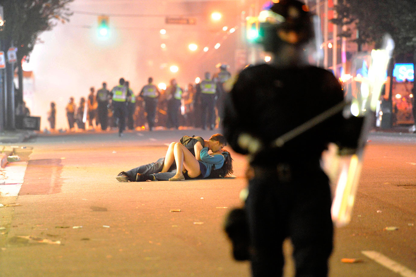While the Boston Bruins celebrated their championship inside Rogers Arena, a riot broke out in the normally peaceful city of Vancouver after fans left the building. While police patrolled and tried to contain the commotion, an amorous couple kissed in the street.