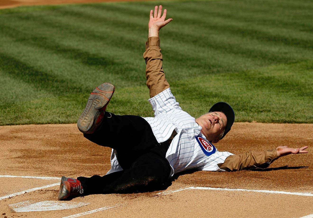 Bill Murray slides into home after rounding the bases before throwing out the ceremonial first pitch for the Chicago Cubs game against the Washington Nationals during opening day on April 5, 2012 at Wrigley Field in Chicago.