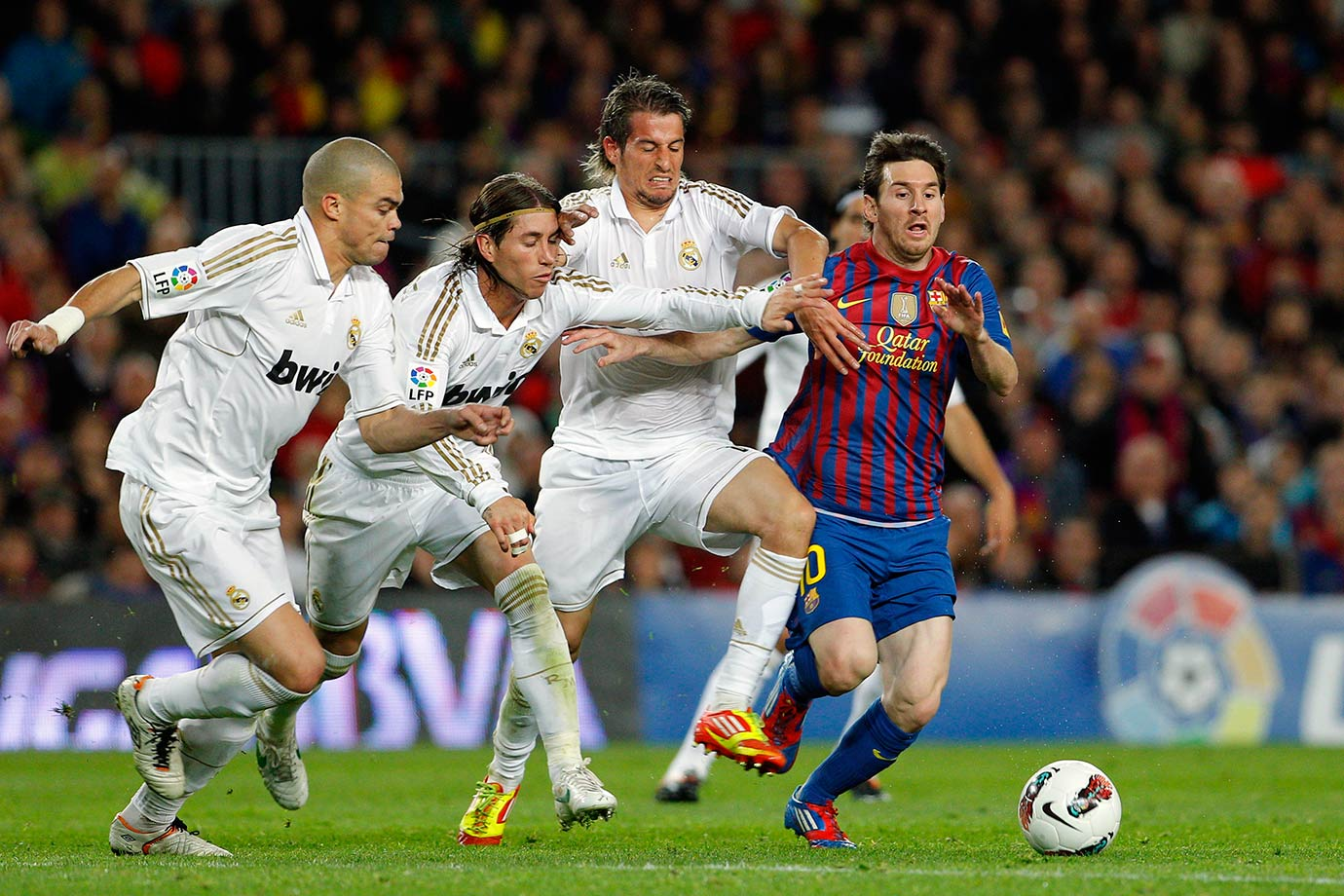Barcelona's Lionel Messi duels for the ball with Real Madrid's Pepe, Sergio Ramos and Fabio Coentrao during their La Liga match on April 21, 2012 at the Camp Nou stadium in Barcelona, Spain.
