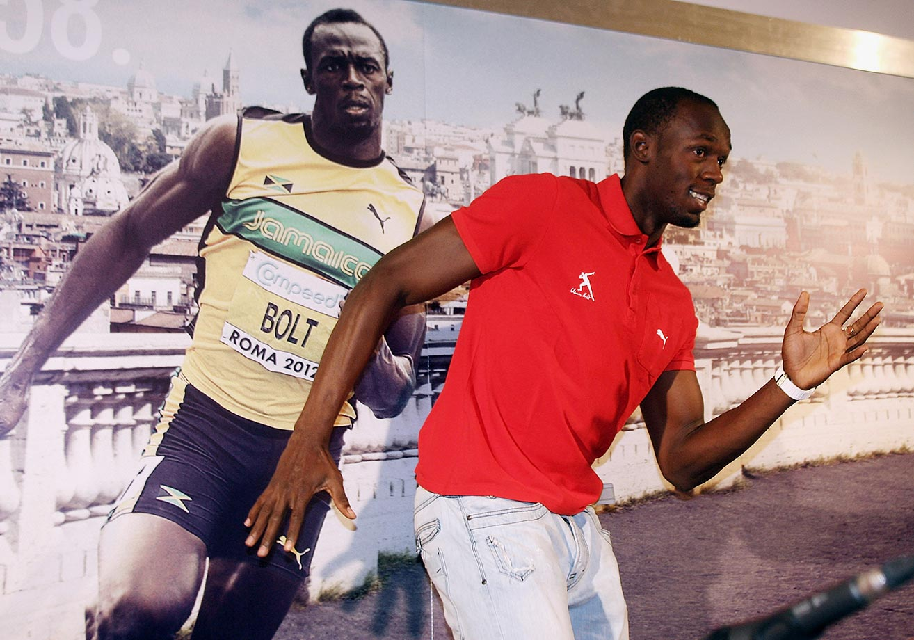 Usain Bolt re-enacts a photo of himself at a 2012 IAAF Golden Gala press conference in Rome.