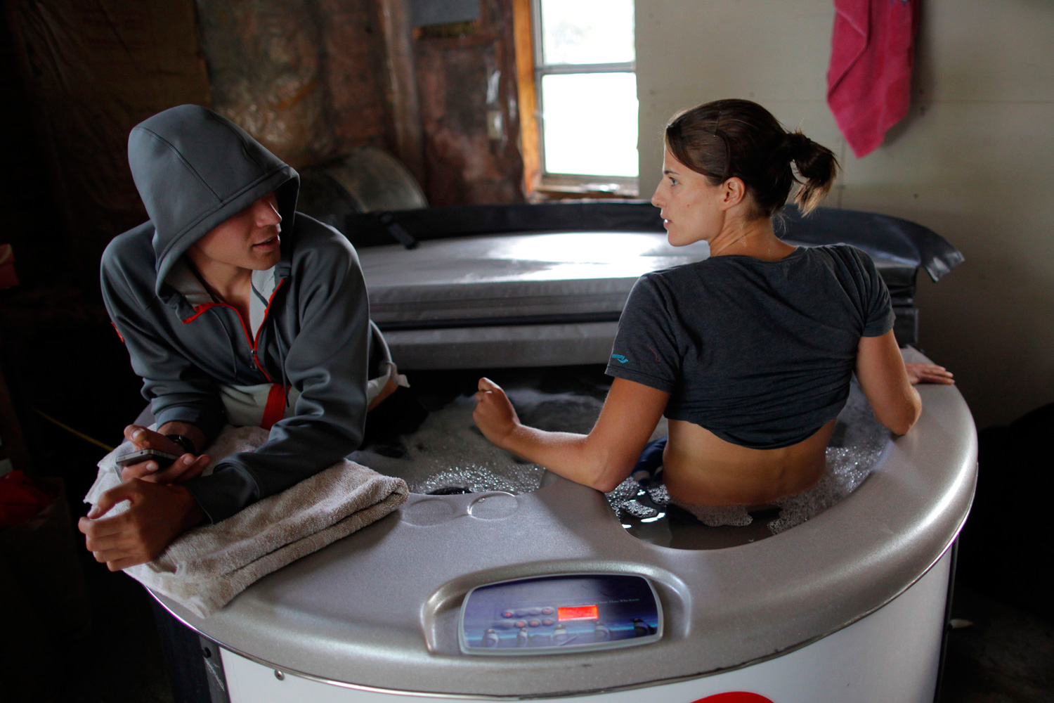 U.S. Olympic tri-athlete Sarah Groff, also the winner of the 2007 ITU Aquathlon World Championships, and her boyfriend Ben True (L) sit in an ice bath at their home in Hartford, Vermont after a day of training.