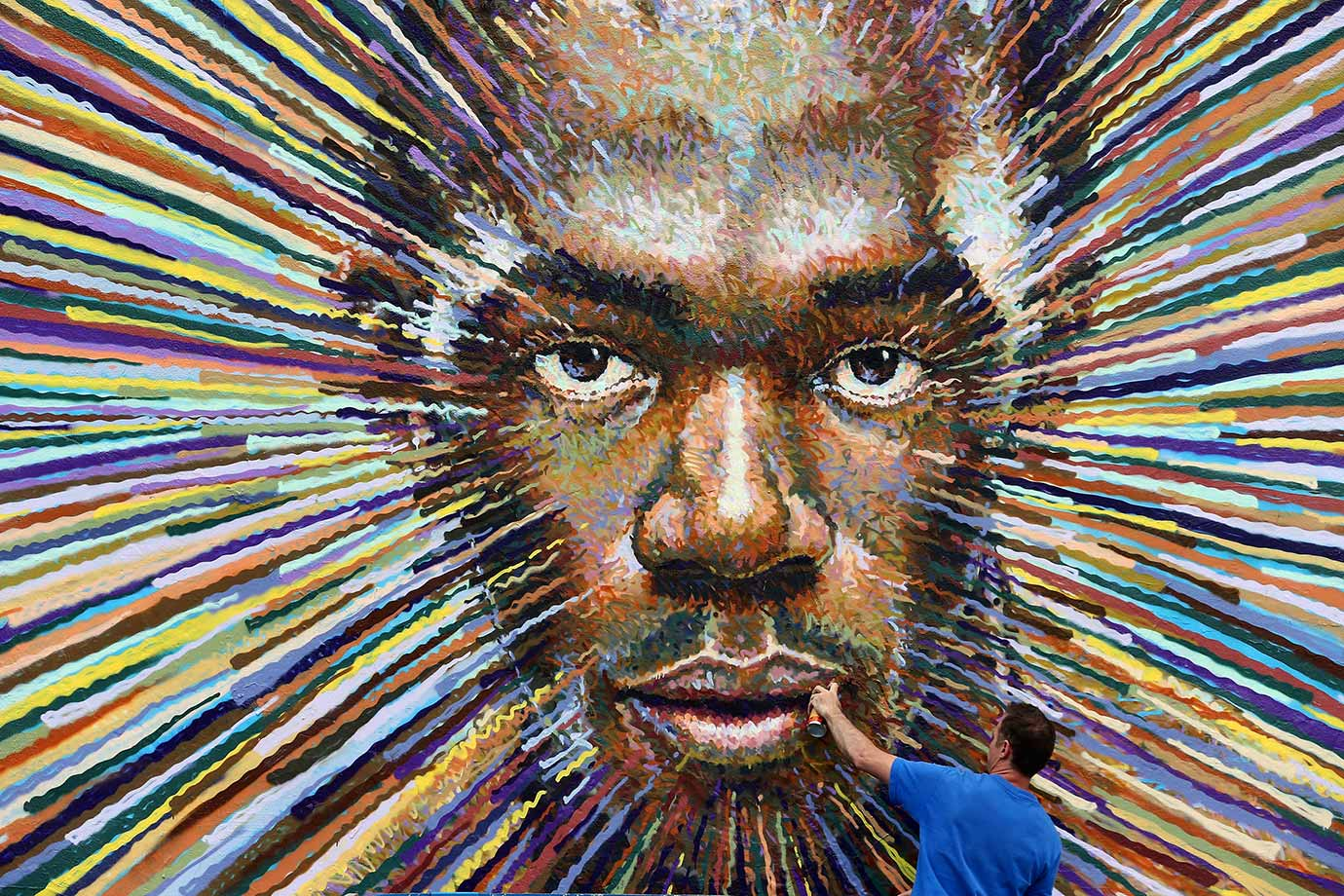 Street artist James Cochran puts the finishing touches on a piece depicting the face of Usain Bolt in London as a lead-up to the opening of the 2012 London Olympic Games.