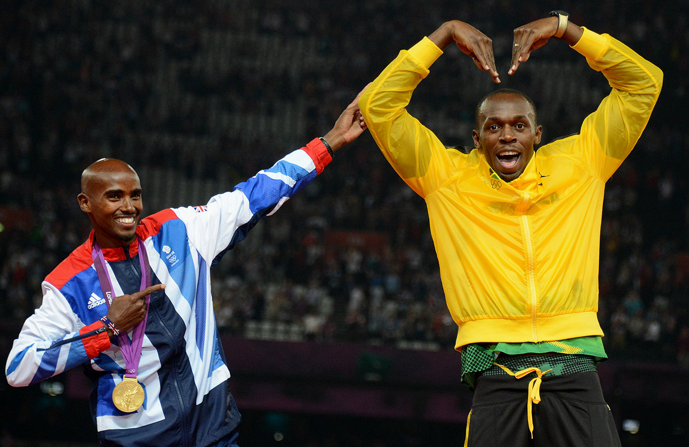 Usain Bolt has fun with Great Britain's 5000-meter gold medalist Mohamed Farah during the 2012 London Olympic Games.