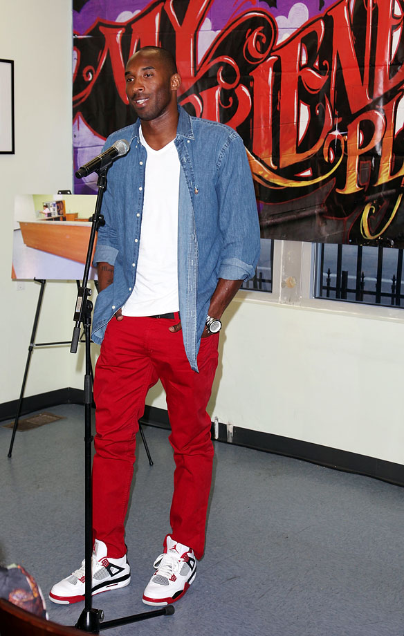 Kobe rocks red pants and Air Jordans while speaking at a 2012 press conference for the Kobe and Vanessa Bryant Family Foundation.