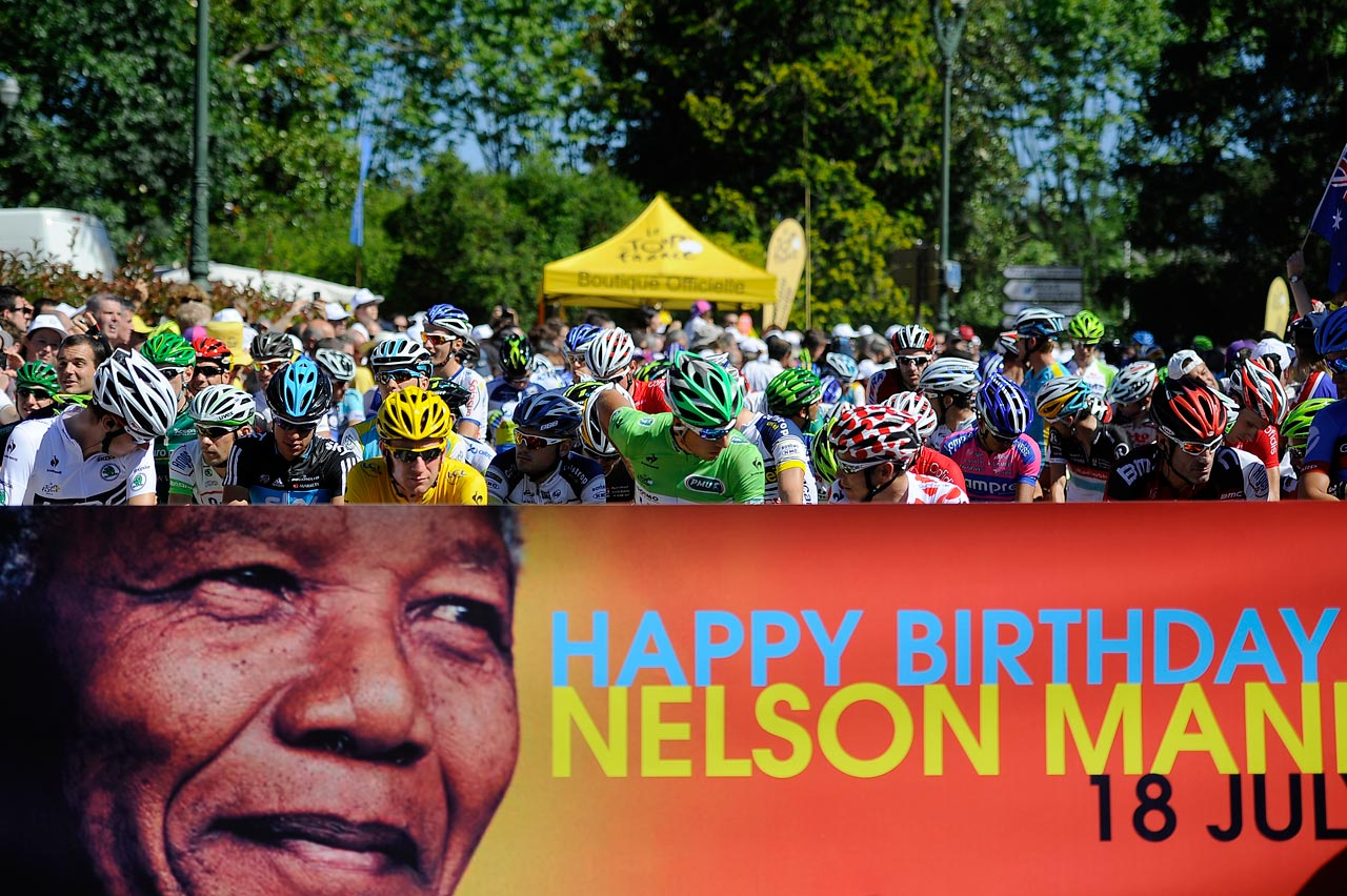 Prior to the 16th stage of the 2012 Tour de France, cyclists wait behind a poster that celebrates Mandela's 94th birthday.