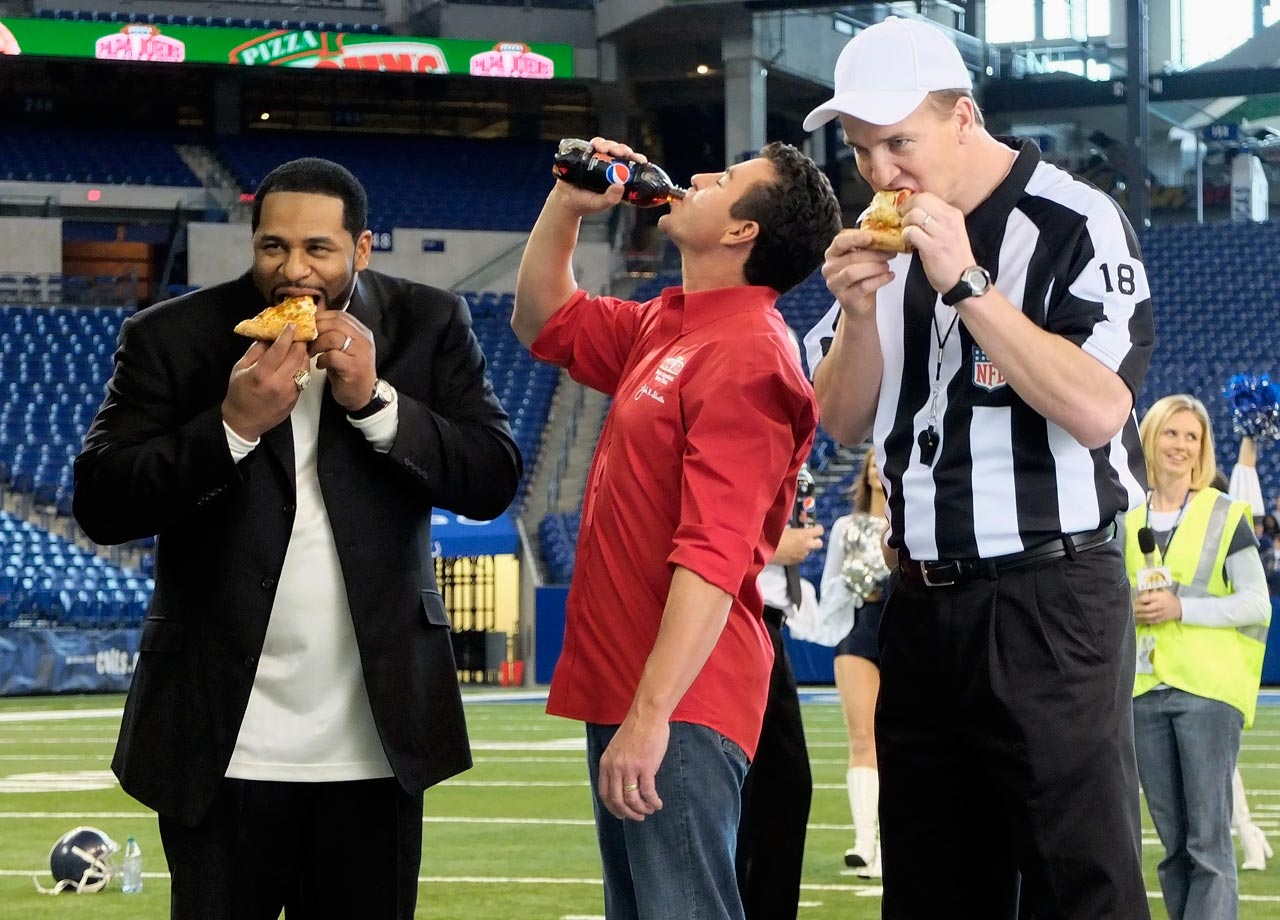 Jerome Bettis and Peyton Manning eat some Papa John's pizza alongside Founder, Chairman and CEO John Schnatter during a commercial shoot at Lucas Oil Stadium in Indianapolis.