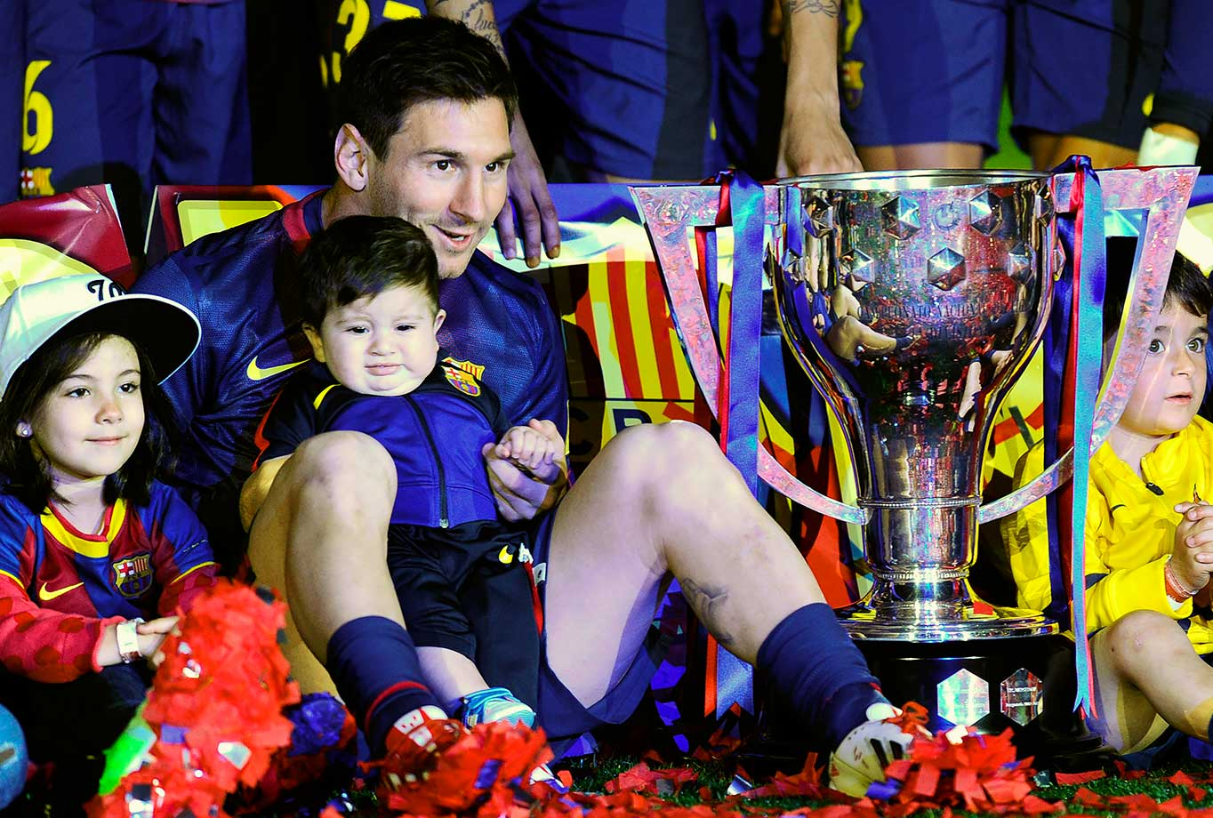Barcelona's Lionel Messi holds his son Thiago as they sit next to the trophy after winning the La Liga match against Real Valladolid on May 19, 2013 at Camp Nou stadium in Barcelona, Spain.