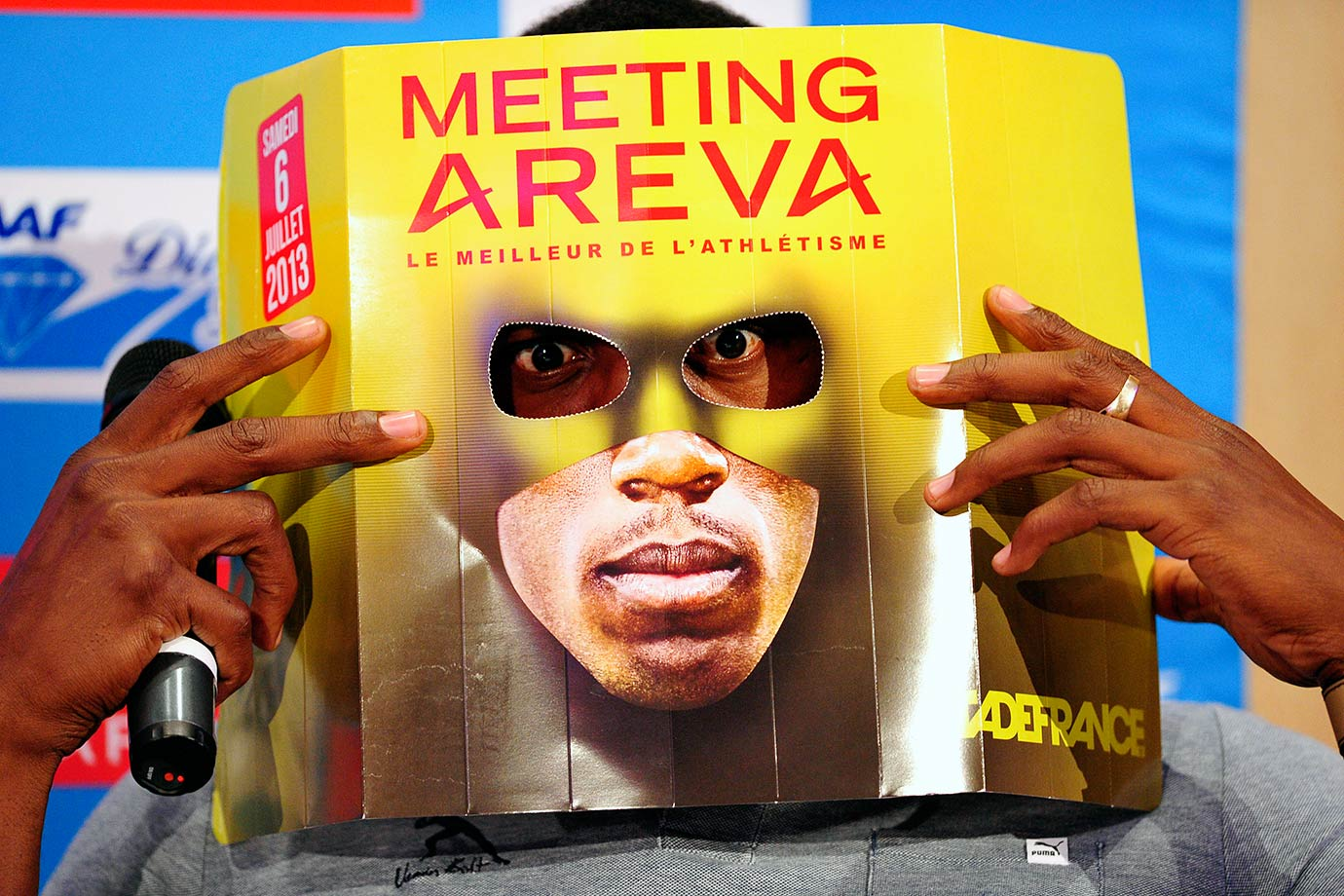 Usain Bolt looks through a leaflet displayed as a mask as he poses after a 2013 press conference in Paris.