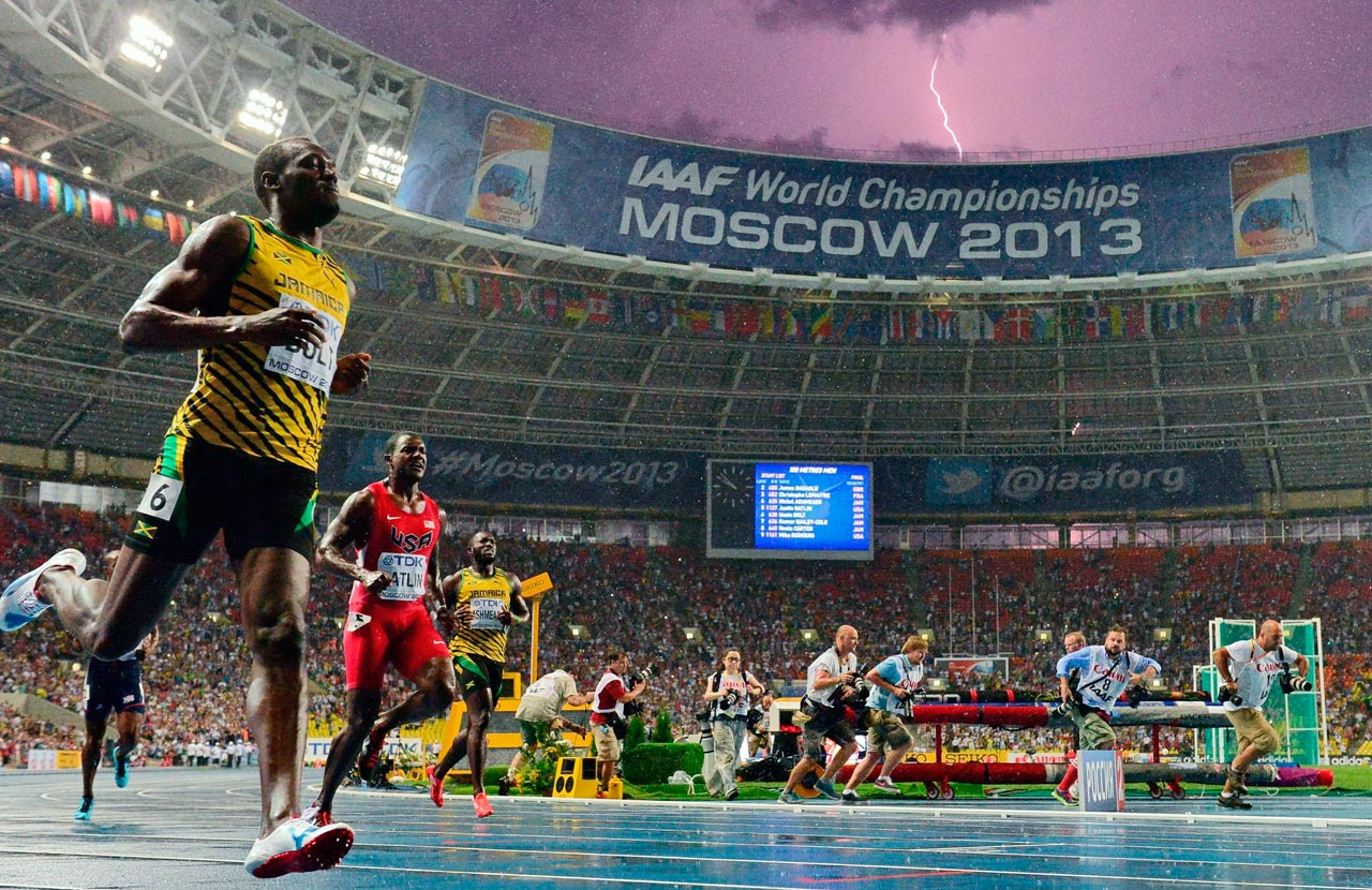 Usain Bolt wins the 100m final at the 2013 IAAF World Championships while a lightning bolt strikes in the sky above Luzhniki Stadium in Moscow.
