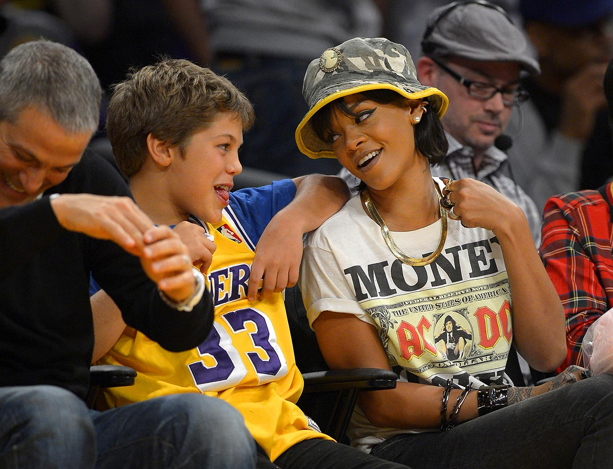 Rihanna talks with talent agent Ari Emanuel and his son Leo as they watch the Los Angeles Lakers game against the Golden State Warriors on Nov. 22, 2013 at Staples Center in Los Angeles.