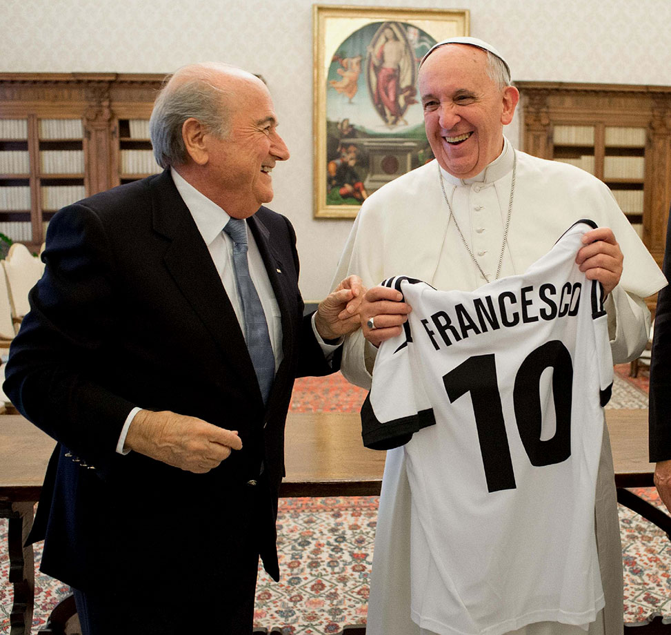 Pope Francis smiles as he receives a jersey from FIFA President Sepp Blatter during a private audience at The Vatican on November 22, 2013 in Vatican City.