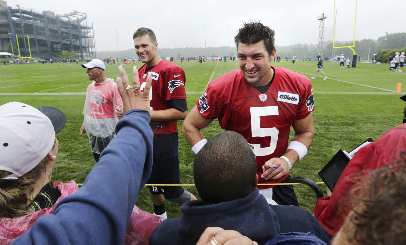 Patriots quarterbacks Tim Tebow and Tom Brady talk with fans and sign autographs following practice at training camp in Foxborough, Mass. The Pats released Tebow on Aug. 31.
