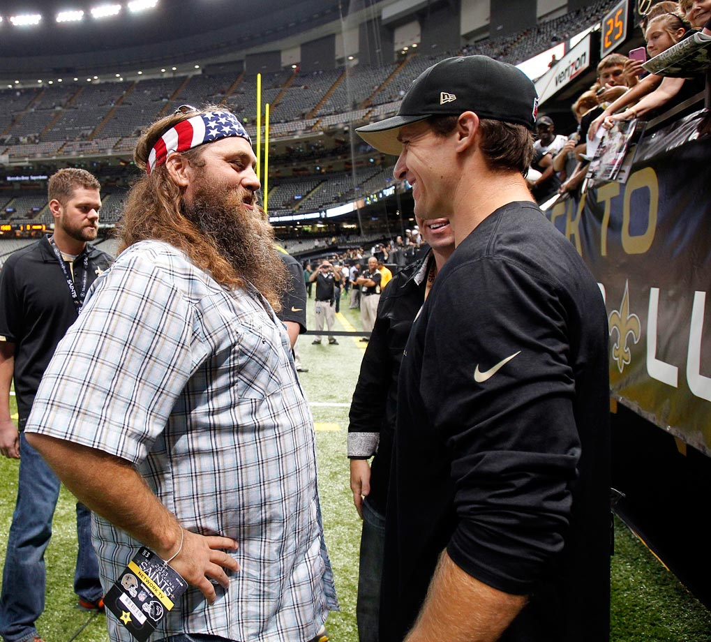 """Duck Dynasty"" star Willie Robertson chats with Drew Brees on the field before the Saints' game against the Atlanta Falcons in New Orleans."