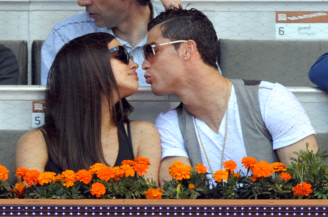 Cristiano Ronaldo leans in to kiss Irina Shayk as they attend the Mutua Madrid Open tennis tournament at La Caja Magica.