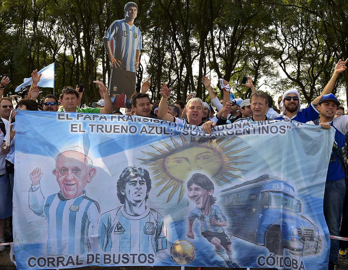 Argentina's supporters hold a banner depicting Pope Francis, Diego Maradona and Lionel Messi as they wait for the arrival of Argentinian players outside the Beira-Rio Stadium in Porto Alegre, on June 24, 2014, on the eve of a Group F football match between Argentina and Nigeria during the 2014 FIFA World Cup in Brazil.