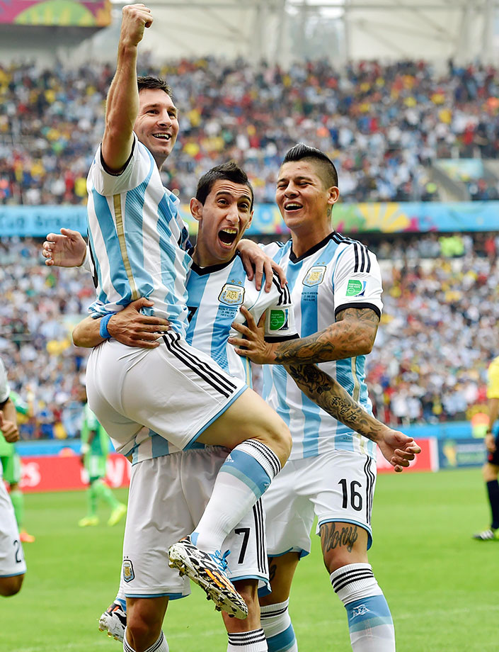 Argentina's Lionel Messi celebrates with teammates Angel di Maria and Marcos Rojo after scoring their first goal during the FIFA World Cup Group F match against Nigeria on June 25, 2014 at the Estadio Beira-Rio in Porto Alegre, Brazil.