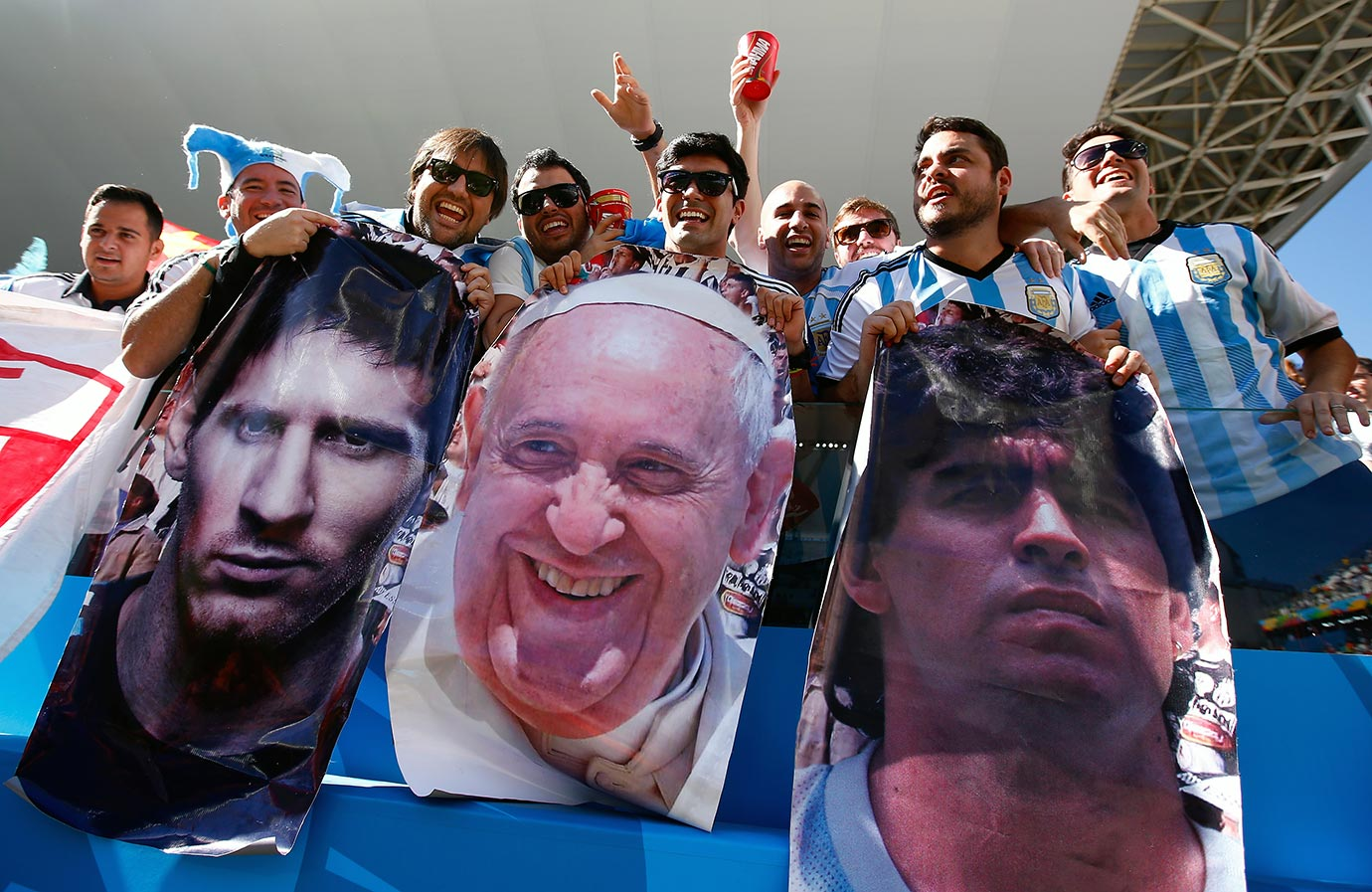 Argentina fans hold posters of Lionel Messi, Pope Francis and Diego Maradona prior to the 2014 FIFA World Cup Brazil Round of 16 match between Argentina and Switzerland at Arena de Sao Paulo on July 1, 2014 in Sao Paulo, Brazil.