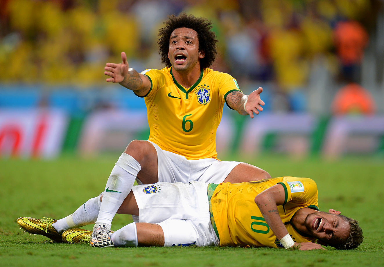 Neymar lies injured while teammate Marcelo appeals during Brazil's World Cup quarterfinal match against Colombia on July 4, 2014 at Estadio Castelao in Fortaleza, Brazil.
