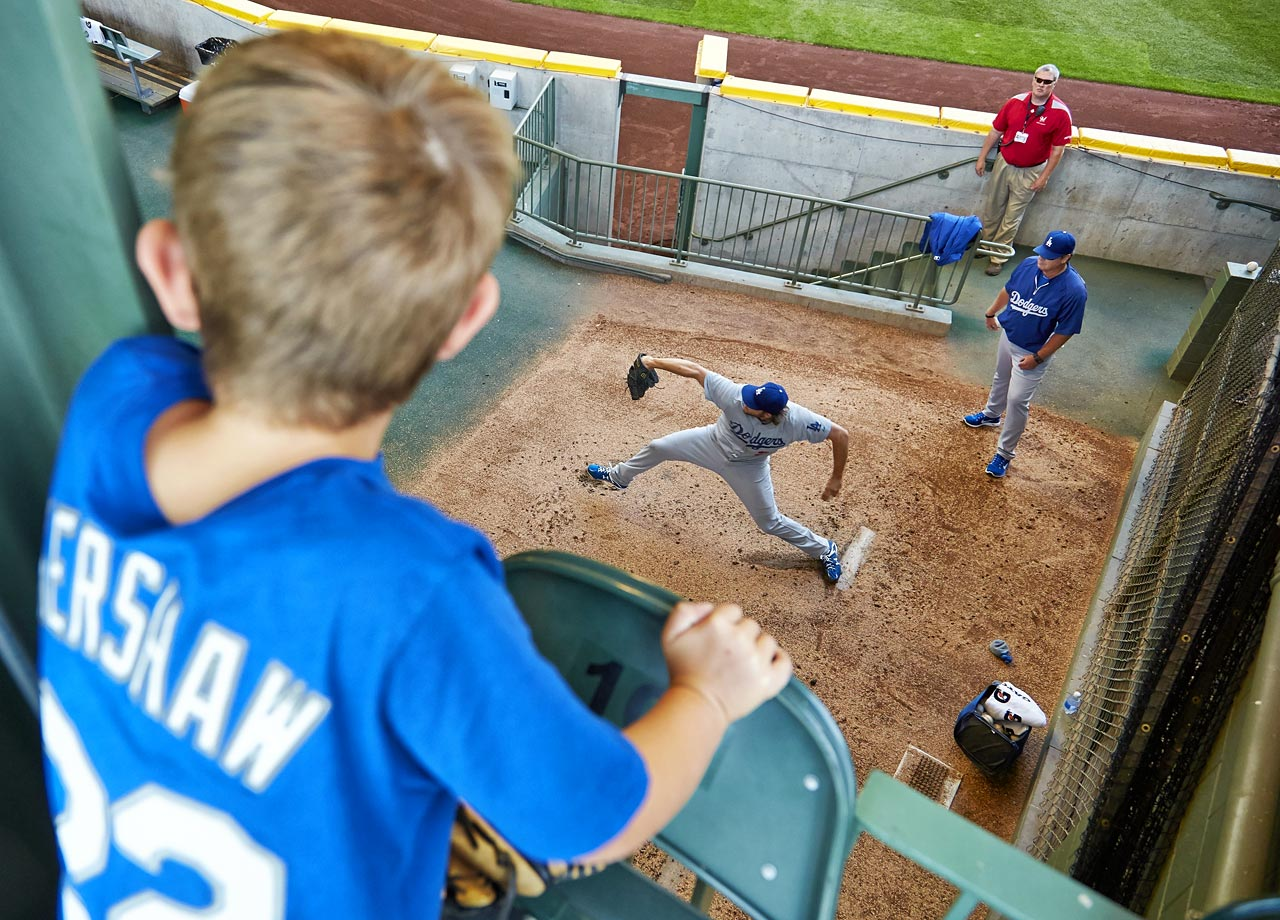 A young fan of Clayton Kershaw watches the Dodgers' pitcher warmup in the bullpen before starting against the Brewers at Miller Park on Aug. 10, 2014 in Milwaukee, Wisc.
