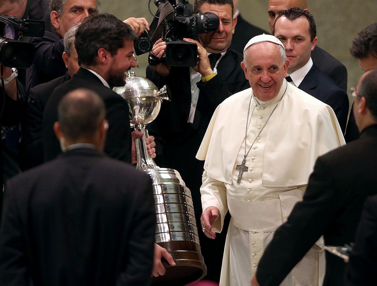 Pope Francis receives the Copa Libertadores trophy from Matias Lammens as he meets members of the San Lorenzo team during his weekly public audience on August 19, 2014 in Vatican City.