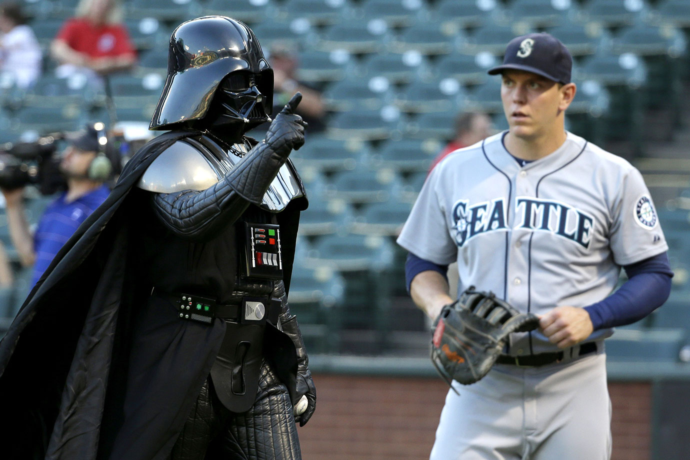 Darth Vader points to fans as he walks by Seattle Mariners first baseman Logan Morrison after throwing out the ceremonial first pitch before the Mariners game against the Texas Rangers on Sept. 5, 2014 at Rangers Ballpark in Arlington, Texas.