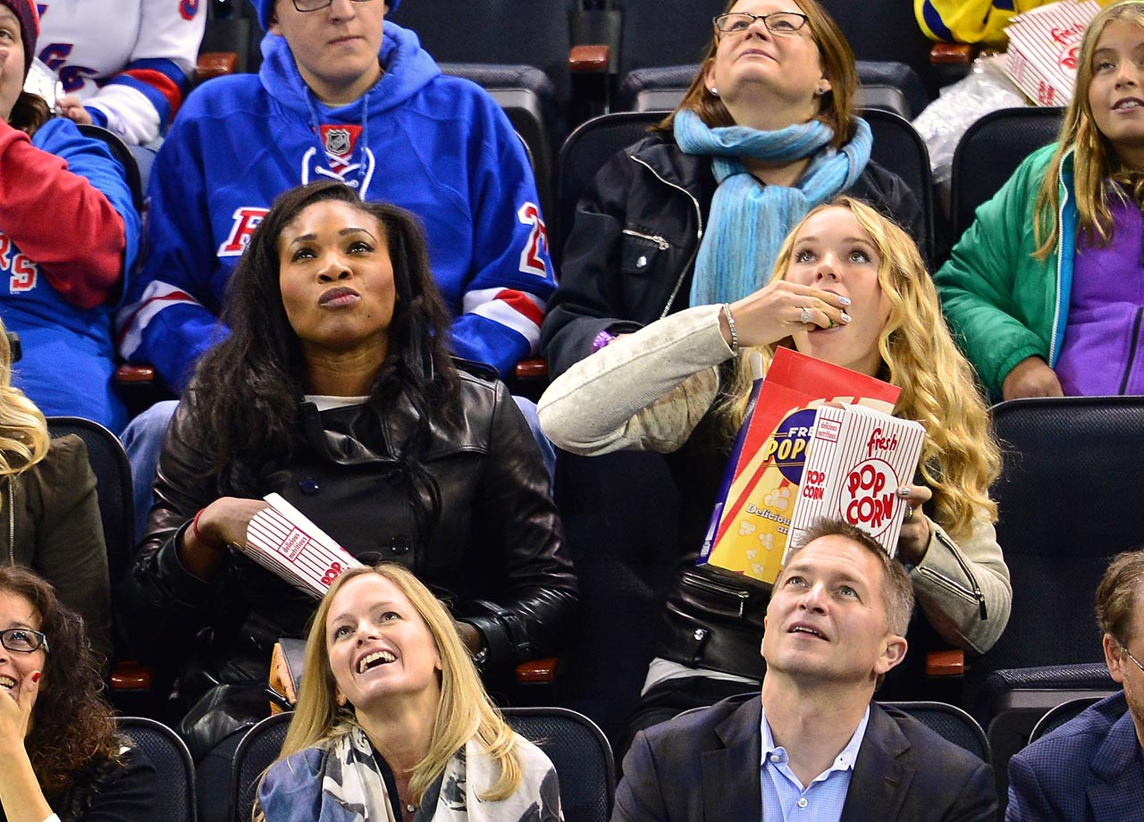 Serena Williams and Caroline Wozniacki enjoy some popcorn during the New York Rangers game against the Winnipeg Jets at Madison Square Garden on Nov. 1, 2014 in New York City.