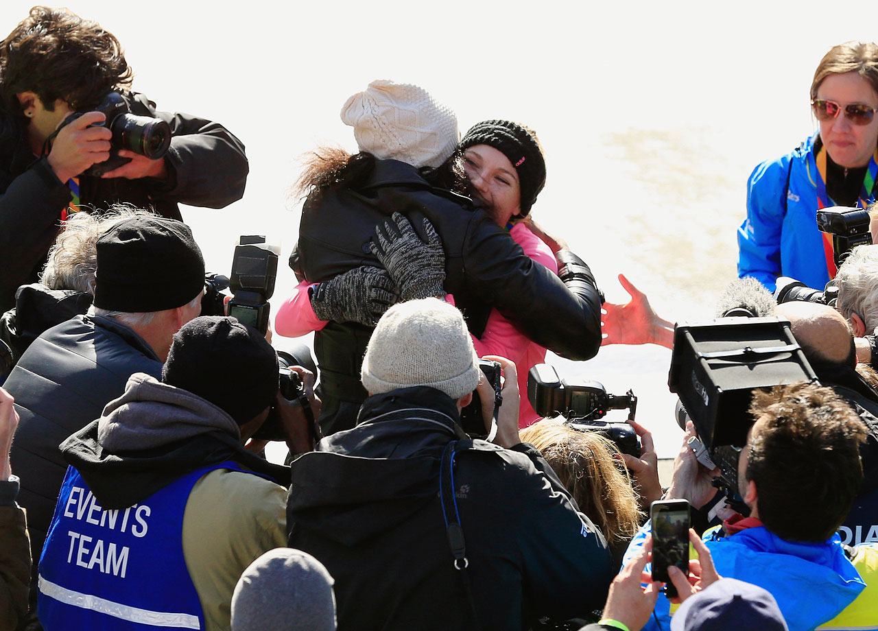 Serena Williams and Caroline Wozniacki hug as the media looks on after Wozniacki finished the New York City Marathon in Central Park on Nov. 2, 2014 in New York City.