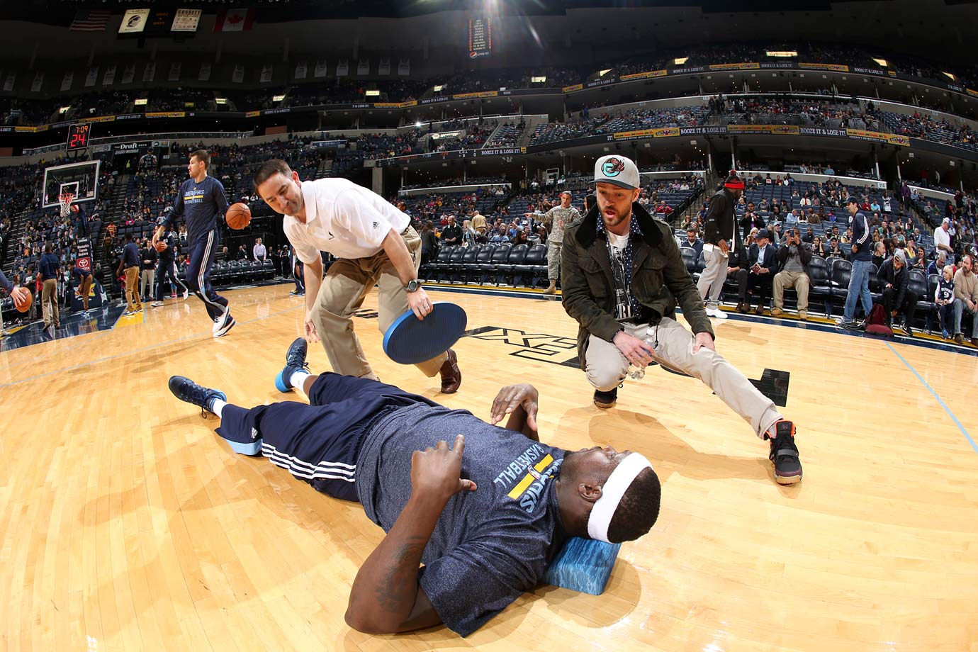 Justin Timberlake stretches alongside Zach Randolph prior to the Memphis Grizzlies game against the Miami Heat at FedExForum in Memphis, Tenn., on Dec. 7, 2014.