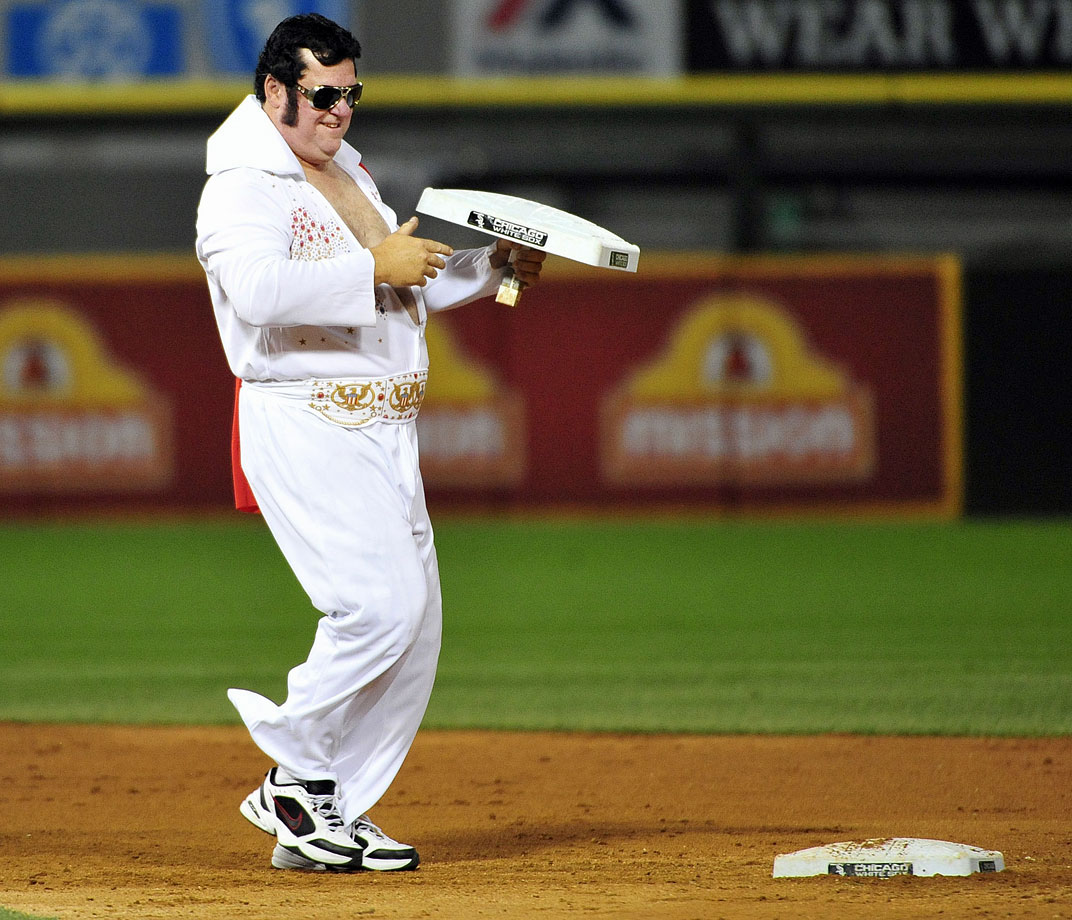 A man dressed as Elvis Presley changes the bases during the fifth inning of a game between the Chicago White Sox and the Minnesota Twins on Elvis night at U.S. Cellular Field in Chicago on Aug. 1, 2014.