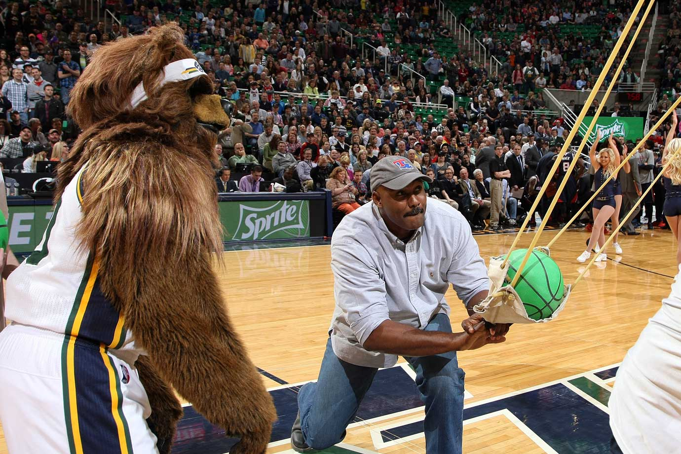 Karl Malone shoots balls into the crowd with help from Utah's mascot Jazz Bear during a break in play.