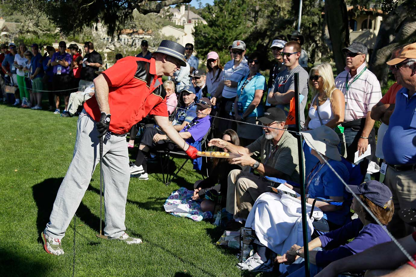 Bill Murray serves a tray of donut holes to fans around the second green during the third round of the AT&T Pebble Beach National Pro-Am golf tournament on Feb. 14, 2015 in Pebble Beach, Calif.